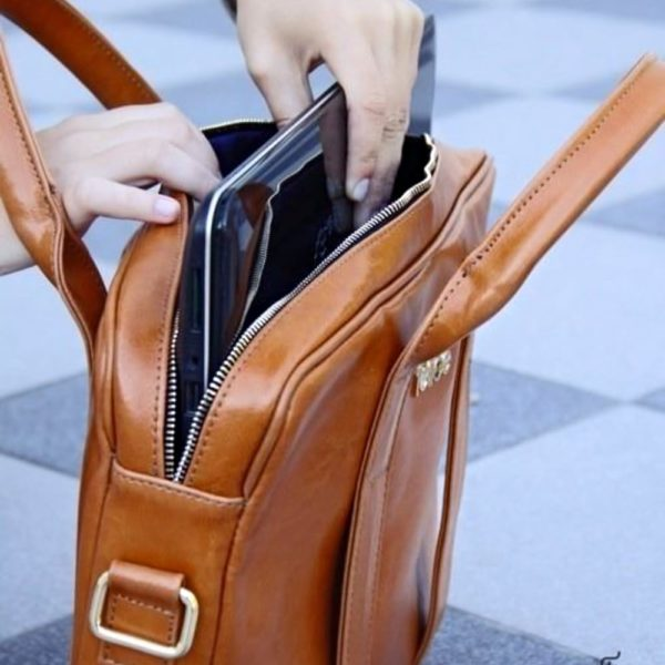 woman putting laptop into a bag
