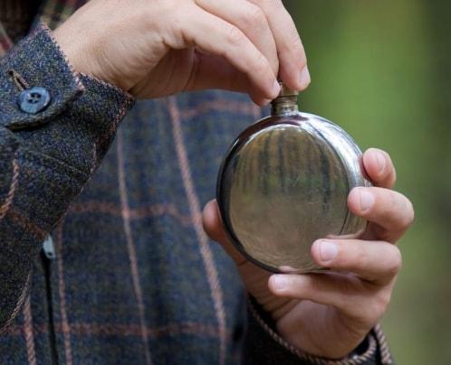 man holding round flask