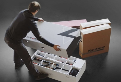 man-opening-delivery-box-contining-bike-parts