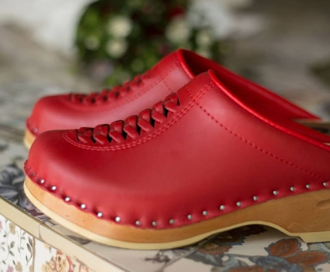 two red leather clogs