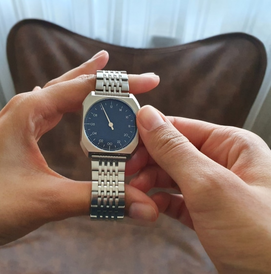 two hands holding one hand watch