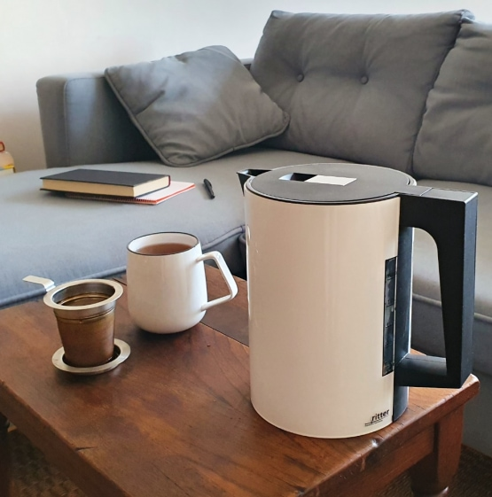 german made white kettle next to a sofa