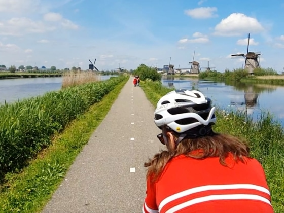 cyclists cycling between canals and windmills in Zaanse Schans