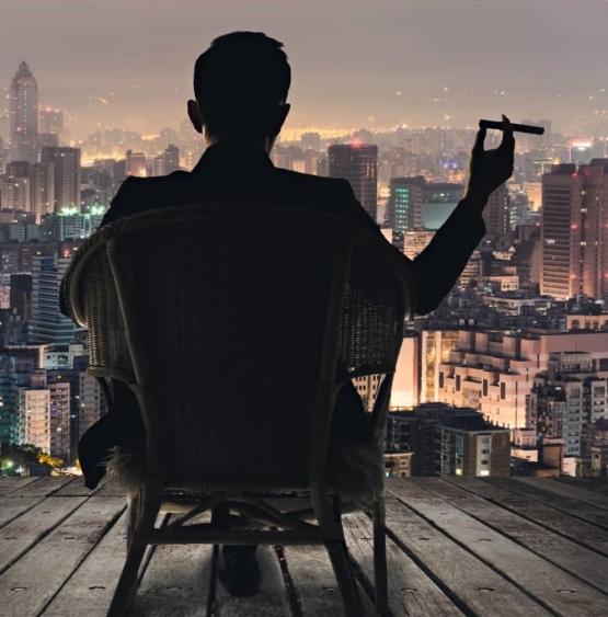 man-sitting-with-cigar-looking-at-the-city-skyline