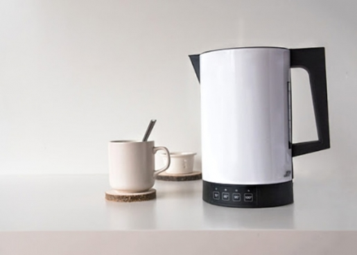 white kettle on the table with a cup